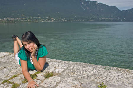 young woman lengthened on a quay at the edge of a lake