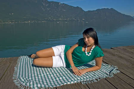 young woman lengthened on a pontoon out of wooden at the edge of a lake Banque d'images