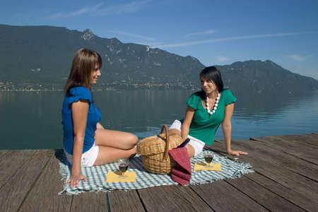 gravitational: Woman making a picnic at the edge of a lake Stock Photo