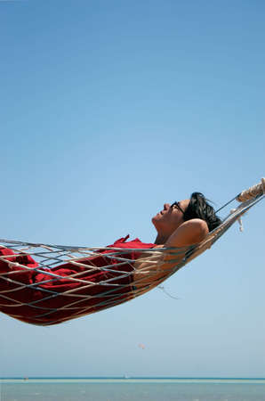 Woman in a hammock on a beach Banque d'images
