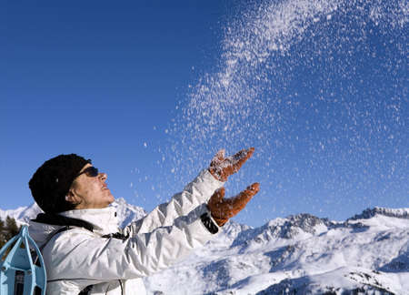 sympathetic: Woman throwing some snow in the air in mountain