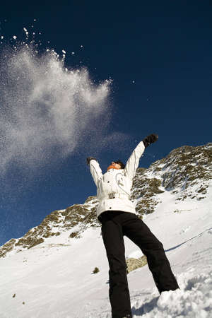 Woman throwing some snow in the air in mountain