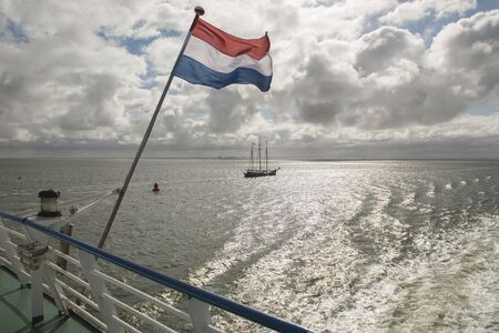 the wadden sea: Wadden Sea with Dutch flag as seen from the ferry Stock Photo