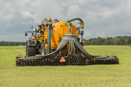 amoniaco: Agricultura, inyección de purín con tractor y remolque esparcidor de buitre amarilla