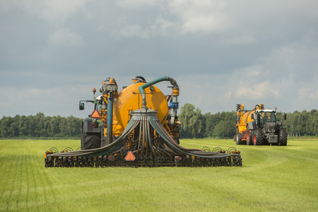 Agriculture, injecting of liquid manure with two tractors and yellow vulture spreader trailers