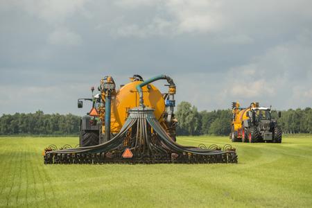 Landbouw, het injecteren van vloeibare mest met twee tractoren en gele gier spreader trailers