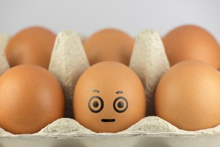 cardboard only: Egg with a face in a egg carton