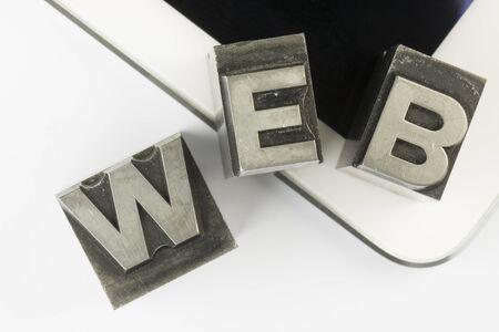 comunicación escrita: Viejas cartas de plomo de tipo de impresión de tinta de una empresa de impresión de libros, como un collage colocado en una tableta moderna. Foto de archivo