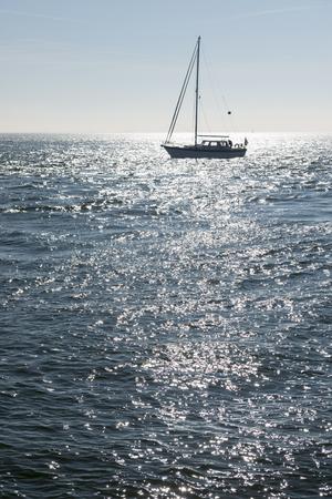 sailingboat: Sailing boat against the glare of the Sun in the sea