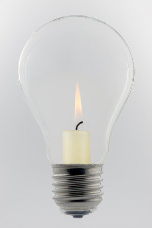 lux: Conceptual glass light bulb with burning candle inside