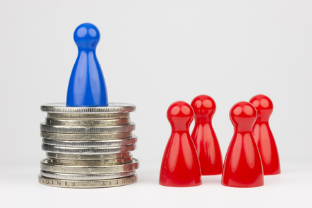 Conceptual financial position Represented play with colored pieces and coins Stock Photo