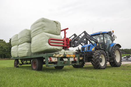 Loading plastic hay bales on a flat cart by a blue tractor Stock Photo