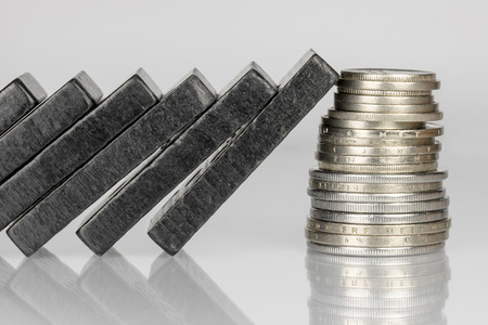 disrupt: Conceptual composition of falling black domino stones as a continuous process and a pile of coins which disrupt this main process Stock Photo