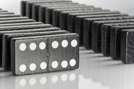 hooking: Composition of standing black domino bricks with white dots Stock Photo