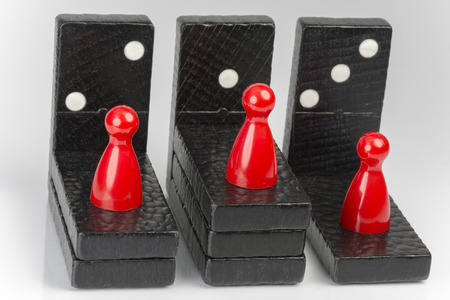 cleave: Conceptual composition of lying and standing domino bricks which express competition Stock Photo