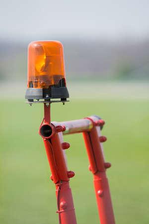 flashing: Orange flashing light on a cell red metal scaffolding