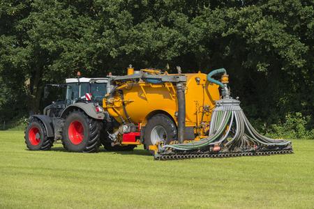 amoniaco: la inyección de estiércol en un pasto con un tractor verde y amarillo del carro tanque buitre en el verano