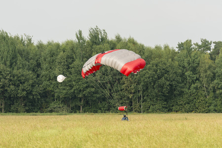 landed: A just landed parachutist with a mattress-shaped parachute in a field
