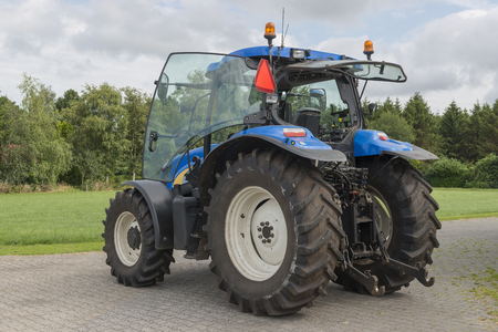 tractor warning: Modern blue tractor on a paved farmyard