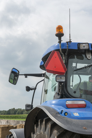 tractor warning: Blue tractor with detail of the truncated warning triangle for motor vehicles with a limited speed on the left side