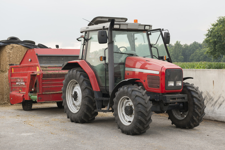 Red tractor with red cattle feed diffuser on a dairy farm Stock Photo
