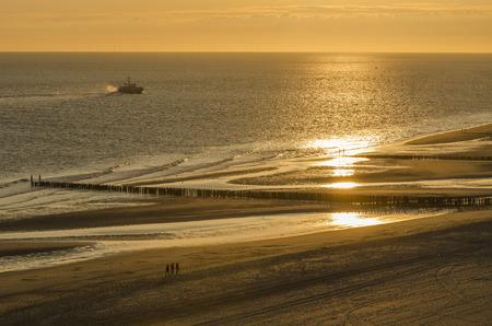 groynes: Walking on the sandy beach of Zoutelande at sunset