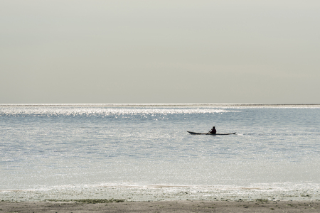 canoeist: Canoeist on the Wadden Sea at Vlieland in the reflection of the sunlight of the water