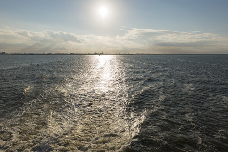 Wake behind the ferry from the Mainland to Vlieland with on the horizon the town of Harlingen in the Netherlands Stock Photo