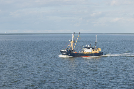 Fishing boat on the Wadden Sea near the island of Vlieland in the North of the Netherlands Stock Photo