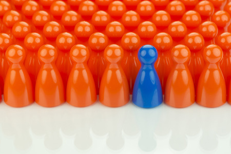 Conceptual orange game pawns and a blue play pawn as abstract display of inequality in color and number of Stock Photo