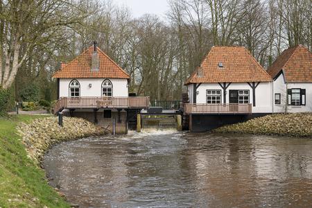 De onlangs gerestaureerde historische watermolen genaamd The Olliemölle of Den Helder in de stroom van de rivier de Boven-Slinge in Winterswijk in Hamlet de Achterhoek in Nederland. De watermolen is een nationaal monument en de restauratie is voltooid