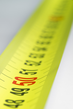 Yellow metal industrial tape measure with standardized metric system such as used in Europe.