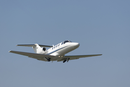 Business Jet directly after takeoff accelerating with withdrawing landing gear