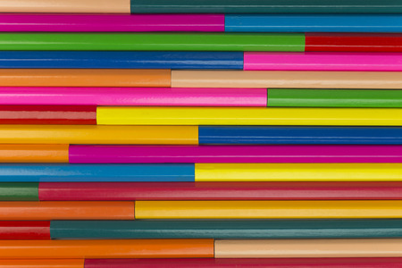 Collection of coloured pencils in a horizontal line pattern as background picture
