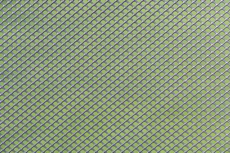 Grey metal wire mesh work against a green background as a background picture Stock Photo