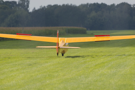 Yellow glider in landing just before the head wheel hits the grass field