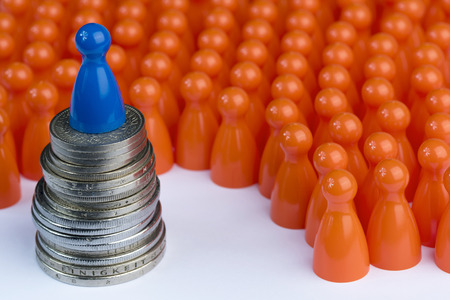 Conceptual orange game pawns as abstract view of a crowd and a blue one on a stack of money
