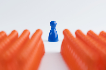 Conceptual orange game pawns and a blue one as abstract view of a crowd