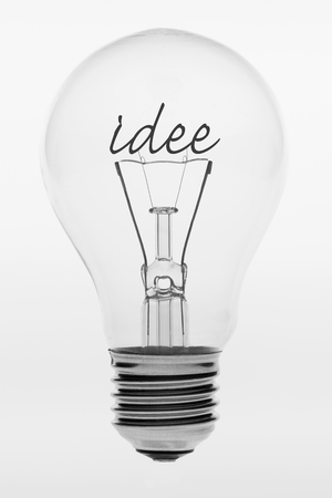 Old fashioned light bulb with the Dutch text idea formed by filaments in the crystal ball