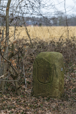 Historical boundary stone on the land border of Netherlands and Germany near the in Dutch called komiezenpaden paths in the past used by border guards and smugglers Banque d'images