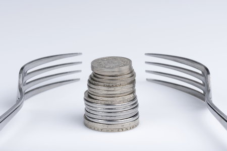 Conceptual representation of financial greed by two forks and coins Archivio Fotografico - 99997221