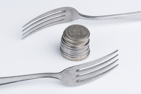 Conceptual representation of financial greed by two forks and coins Archivio Fotografico - 99997222