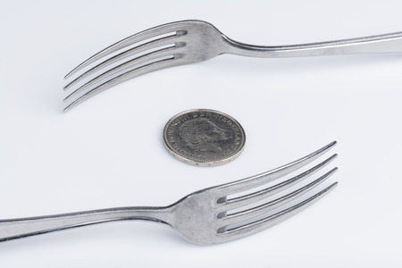 Conceptual representation of financial greed by two forks and coins