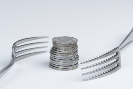 Conceptual representation of financial greed by two forks and coins Archivio Fotografico - 99862403
