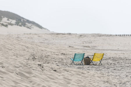 A blue and yellow folding chair on the North Sea Beach of Ameland in the North of Netherlands