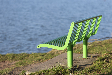 Green bench as street furniture in a grassy area on the waterfront 版權商用圖片
