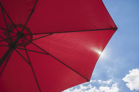 Red beach parasol against a blue sunny summer sky 版權商用圖片
