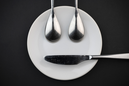 Conceptual face of a ceramic board two metal spoons and a knife