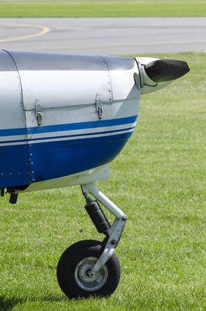 Nose with nose wheel or a single-engine plane on a small sport airfield on the grass