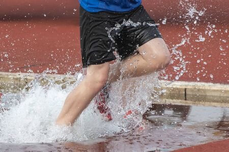 Runner running through the steep chase water bake on a running track